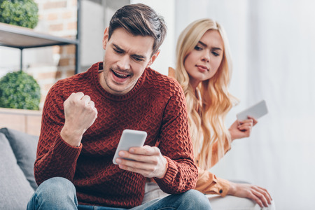 young couple using smartphones at home, excited man shaking fist, distrust concept Stock Photo
