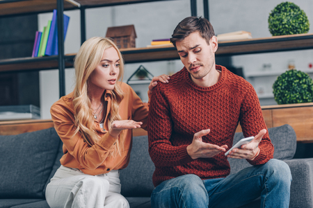 upset young couple sitting on couch and discussing smartphone, distrust concept