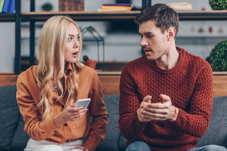 Conmocionada joven sosteniendo el teléfono inteligente y mirando al marido sentado en el sofá, concepto de celos