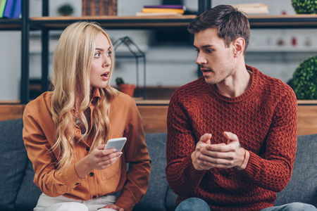 shocked young woman holding smartphone and looking at husband sitting on couch, jealousy concept Foto de archivo - 117397369