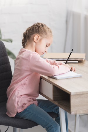 beautiful focused kid sitting at desk and studying at home