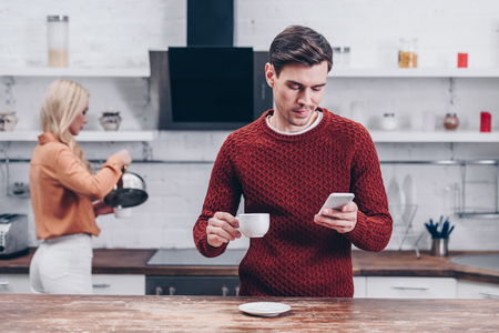 young man holding cup and using smartphone in kitchen, relationship problem concept Stock Photo