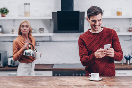 jealous young woman with kettle looking at smiling husband using smartphone in kitchen Stock Photo