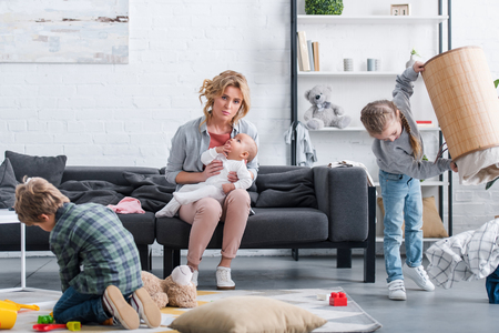 exhausted mother with infant child sitting on couch and looking at camera while naughty siblings playing at home