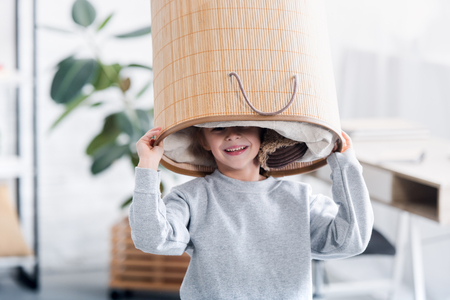 cute happy child playing with laundry basket on head