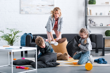 emotional tired mother putting toys in basket while naughty kids fighting with pillows