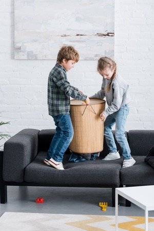 naughty children holding basket on sofa at home
