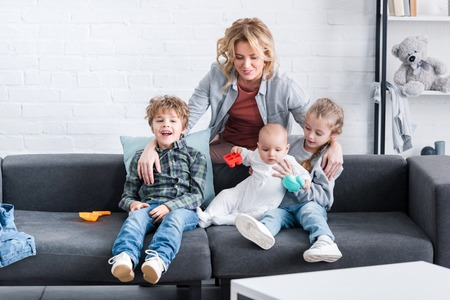 happy mother looking at three adorable kids sitting on couch