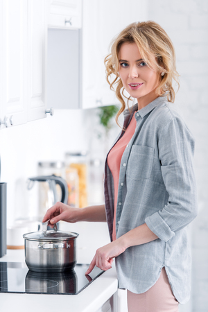 attractive woman cooking and smiling at camera in kitchen