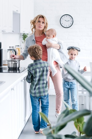 tired mother holding infant child and looking up while naughty children playing in kitchen Stock Photo