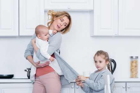 exhausted mother holding infant child while naughty daughter holding her cardigan in kitchen