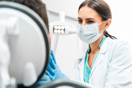 female dentist in mask looking at patient in dental clinic