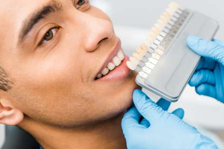 close up of cheerful african american man smiling near teeth color palette