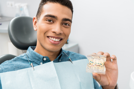 handsome african american man holding dental jaw model with braces