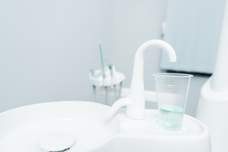 close up of plastic cup with liquid near tap in dental clinic