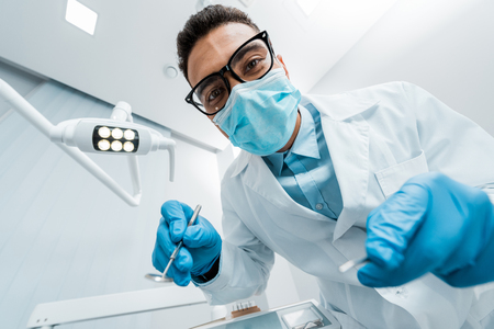 african american stomatologist in glasses and mask with dental instruments in hands