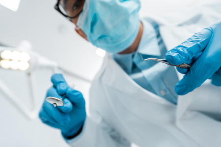 selective focus of dental instruments in hands of male dentist in glasses and mask