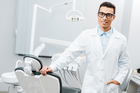 cheerful african american dentist smiling and standing with hand in pocket