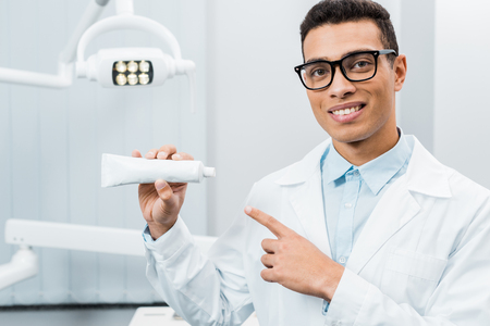 handsome african american doctor showing toothpaste in dental clinic