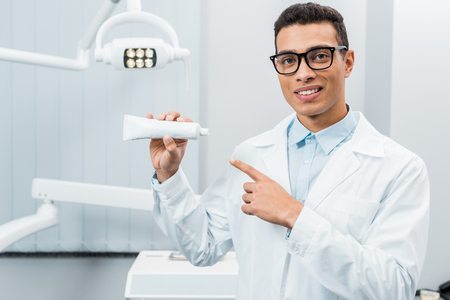 handsome african american doctor in glasses pointing at toothpaste in dental clinic Stock Photo