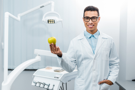 smiling african american dentist with hand in pocket holding apple Stok Fotoğraf