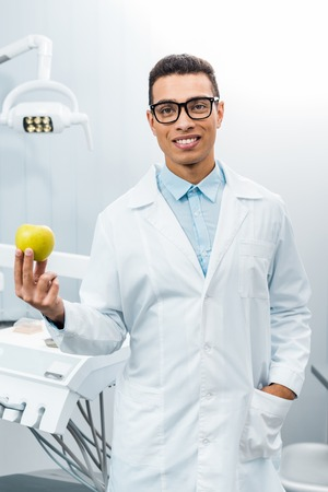 handsome african american dentist with hand in pocket holding apple Stok Fotoğraf