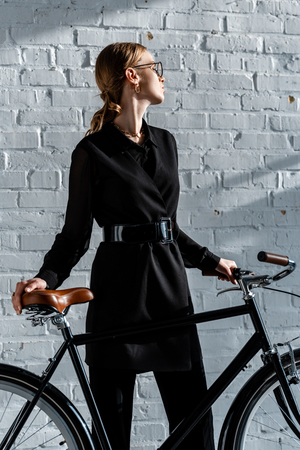 attractive woman in black clothes holding black bike Stock Photo