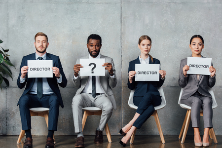 multiethnic businesspeople holding cards with director words and question mark in waiting hall