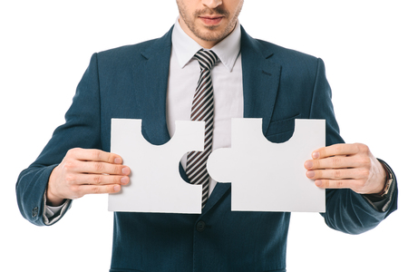 cropped view of businessman holding puzzle pieces isolated on white, business solution concept Banque d'images - 117438490
