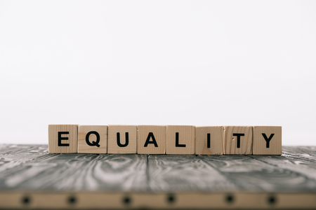 equality word made from alphabet blocks on wooden table on white Foto de archivo - 117438970