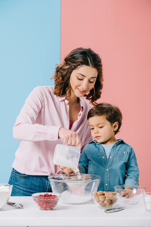 pretty mom with cute little son sifting flour to bowl together on bicolor background