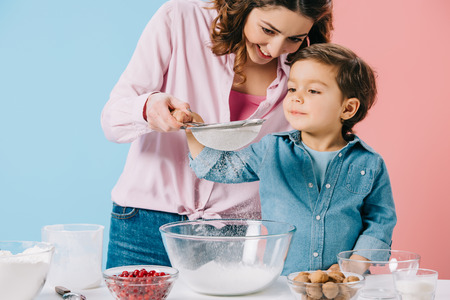 smiling mother with little son sifting flour together on bicolor background