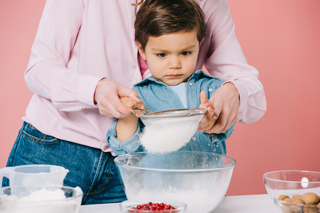 serious little boy sifting flour together with mom isolated on pink Stock Photo