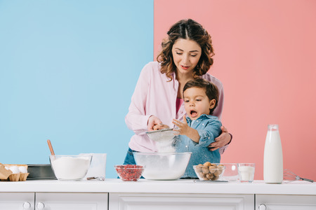 mother with amused little son sifting flour to bowl on bicolor background