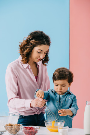 mother helping little son in whipping eggs with balloon whisk on bicolor background