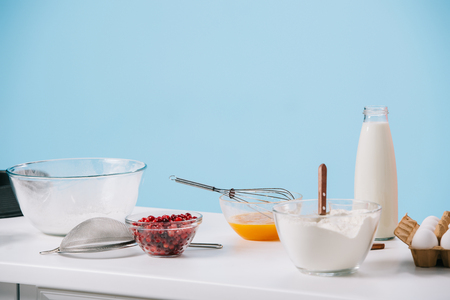 various cooking utensils and products on white kitchen table isolated on blue