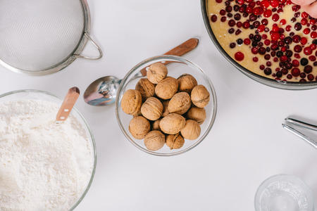 top view of bowls with walnuts and flour, baking form with dough and cranberries, and cooking utensils on white background Archivio Fotografico - 117439179