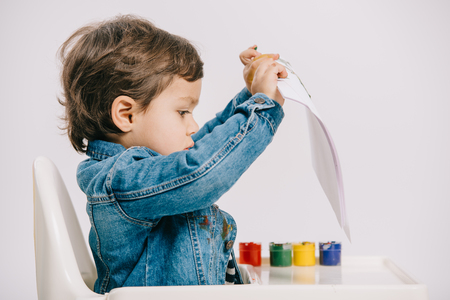 cute little boy holding paper while sitting on highchair with watercolor paints on table isolated on white