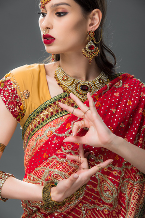 indian woman in traditional sari gesturing isolated on grey