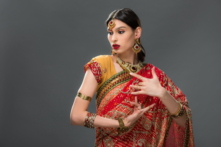 attractive indian woman gesturing in sari and accessories, isolated on grey Фото со стока