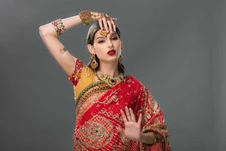 indian woman gesturing in sari and accessories, isolated on grey 版權商用圖片