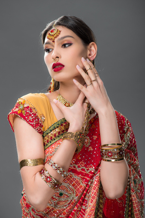 elegant indian woman in sari and accessories, isolated on grey