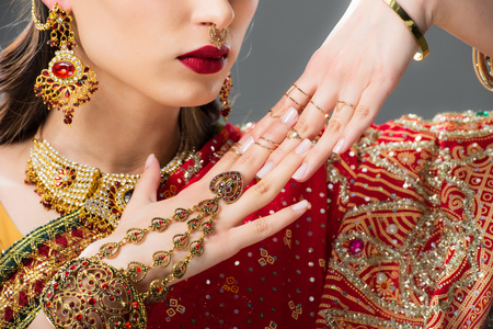 cropped view of attractive indian woman gesturing in traditional accessories, isolated on grey