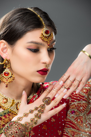 attractive indian woman gesturing in traditional accessories, isolated on grey