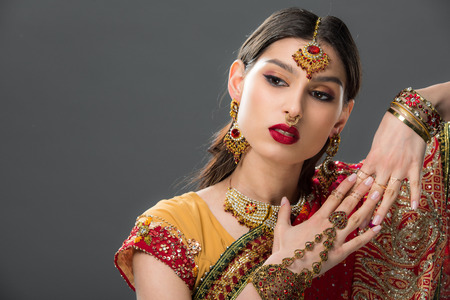 attractive indian woman in sari gesturing isolated on grey