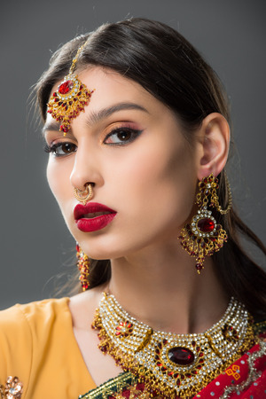beautiful indian woman in sari and accessories, isolated on grey Stock Photo