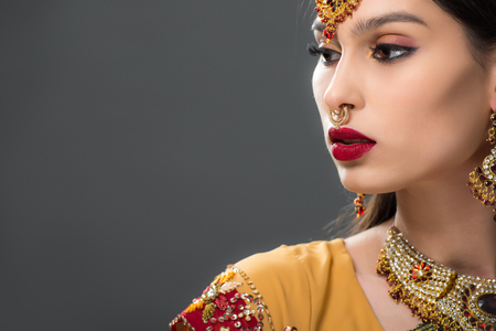 attractive indian woman in traditional sari and accessories, isolated on grey