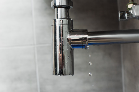 Steel shiny pipe with water drops on grey background