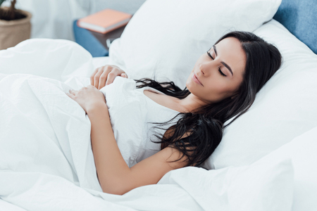 Pretty brunette young woman sleeping in bed Imagens