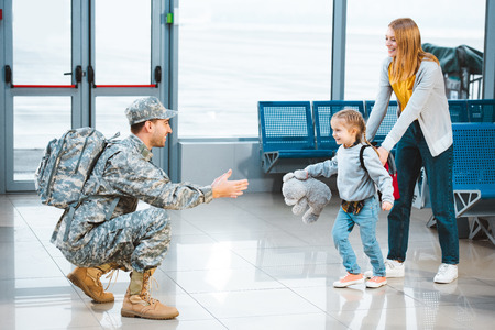 cheerful daughter running to happy father in military uniform in airport